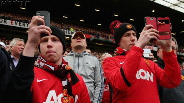 manchester-united-fans-with-mobile-phones-look-on